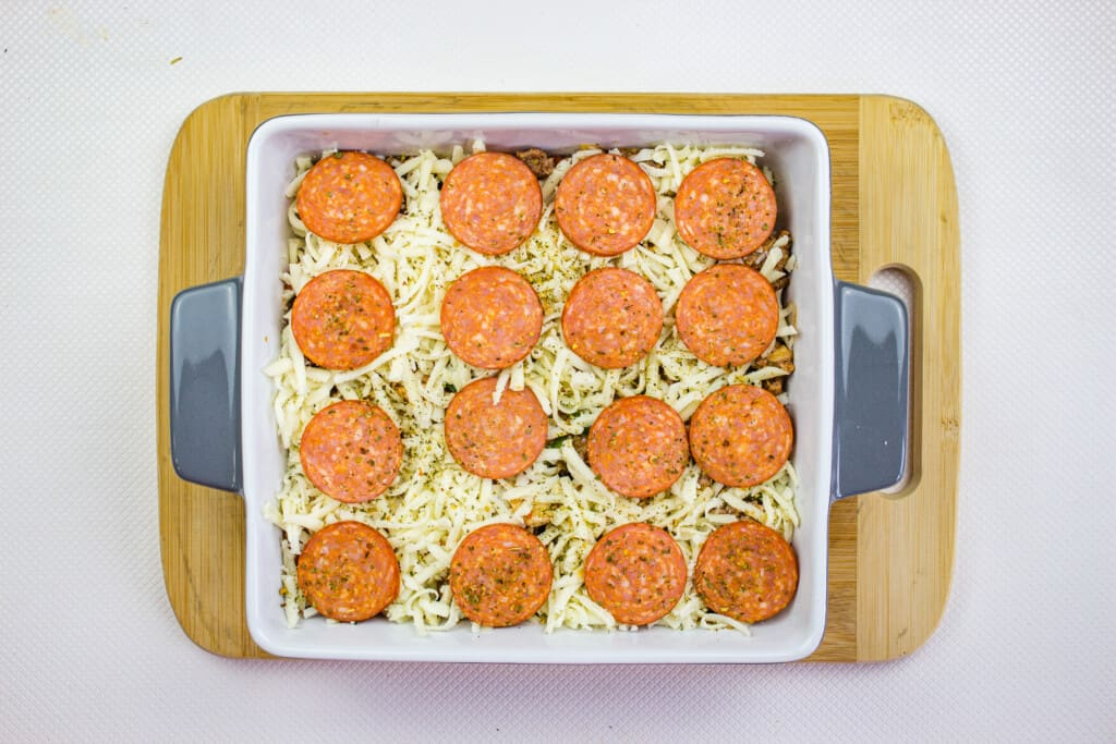 keto pizza casserole topped with cheese and pepperoni