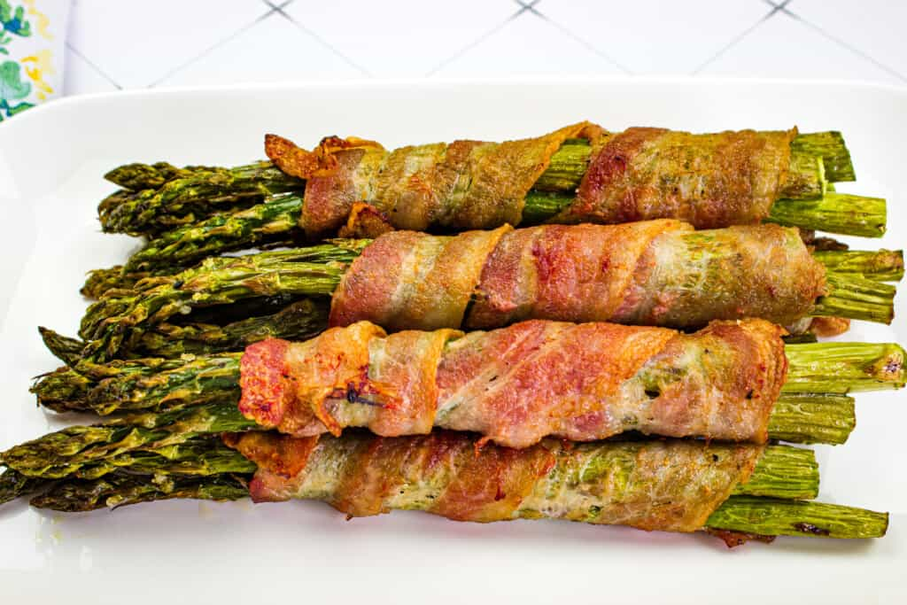 bacon wrapped asparagus air fryer on a white platter