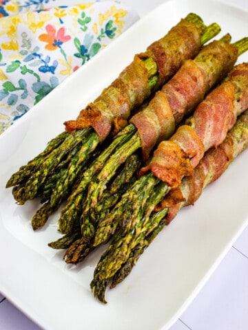 bacon wrapped asparagus on a white platter