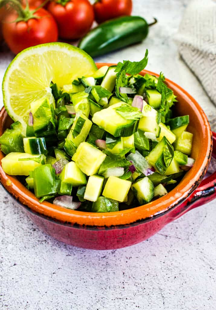 cucumber salsa in a bowl with tomatoes in the background