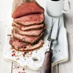 sliced roast beef on a board with a fork