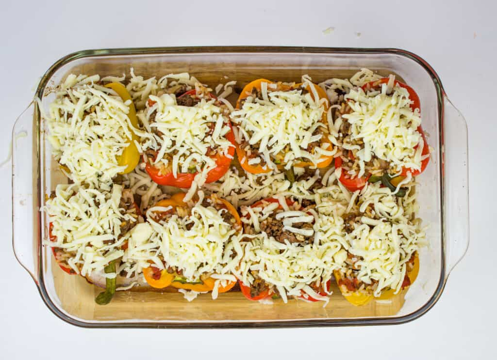 stuffed peppers topped with cheese ready for oven