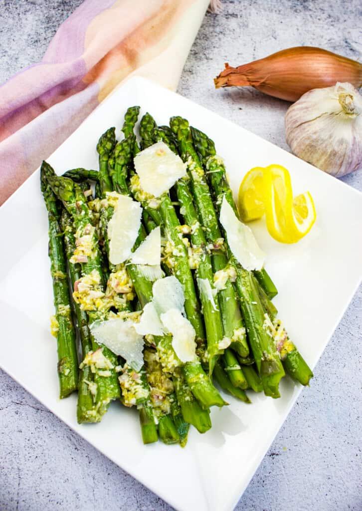 cold asparagus salad with lemon and parmesan on a platter