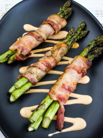 bacon-wrapped grilled asparagus on a black plate