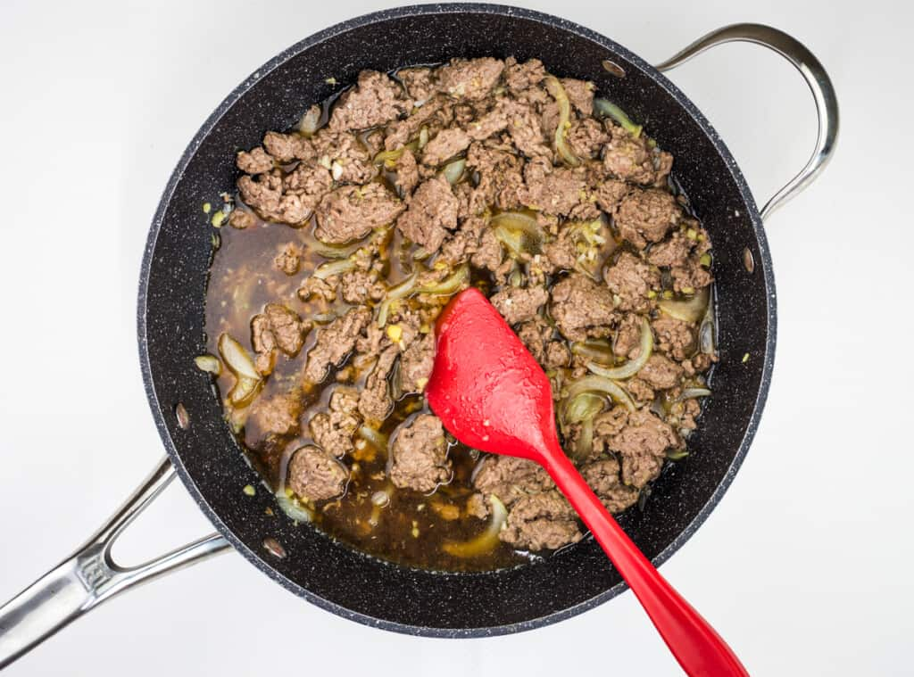 adding sauce and broth to beef