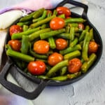 green beans & tomatoes in a black serving dish
