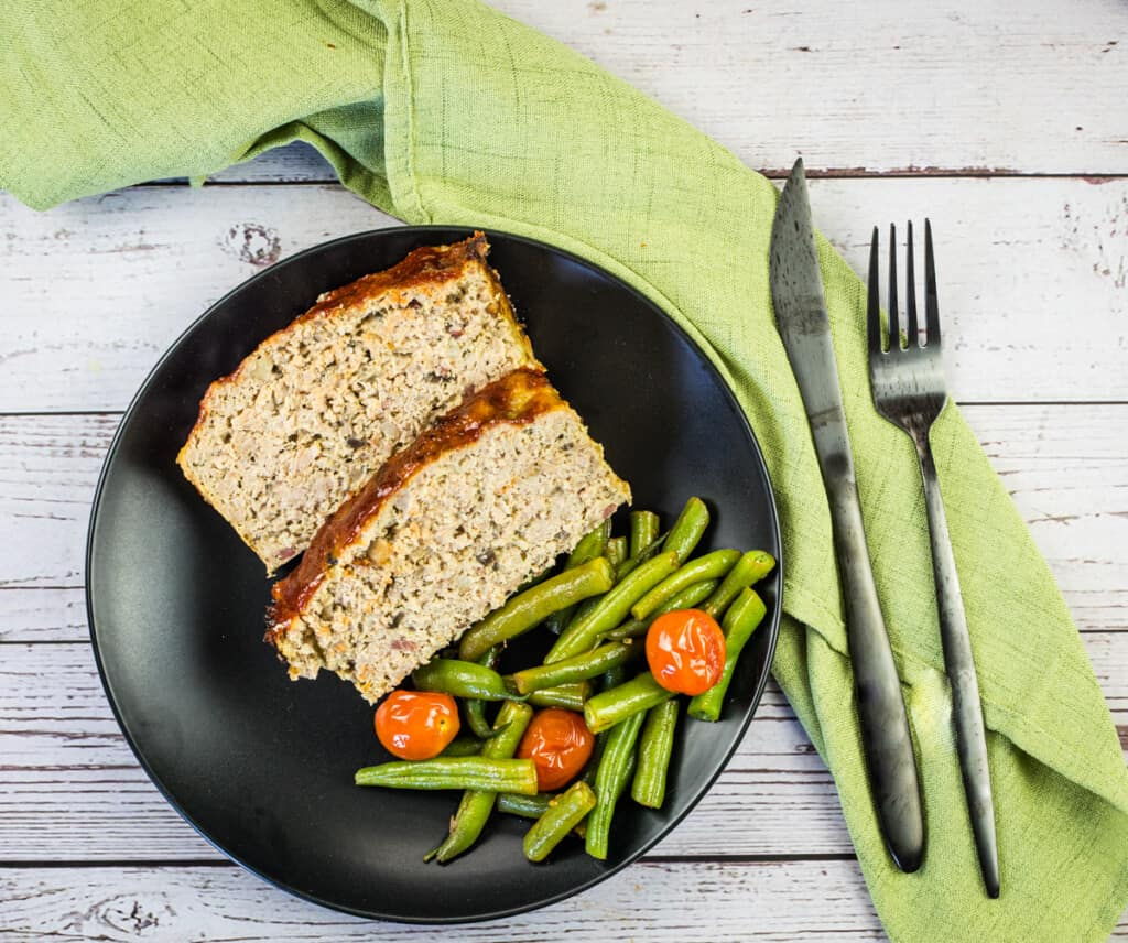 keto turkey meatloaf with bacon on a plate with beans