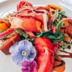 tomatoes, arugula, mozzarella, prosciutto, edible flowers, balsamic glaze, red bell pepper vinaigrette