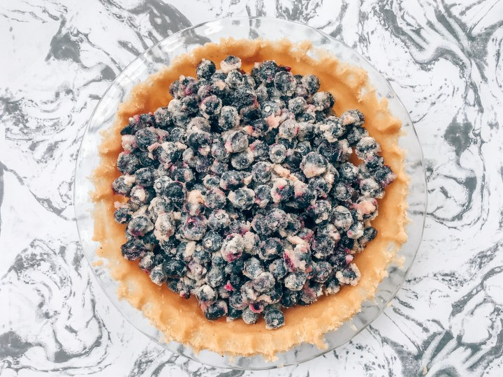Raw pie crust in a glass pie pan filled with blueberries.