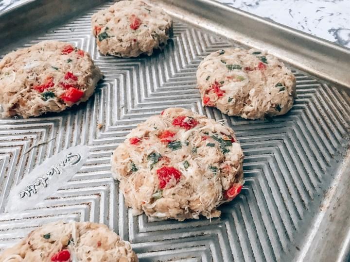 Raw crab cake patty on a baking sheet