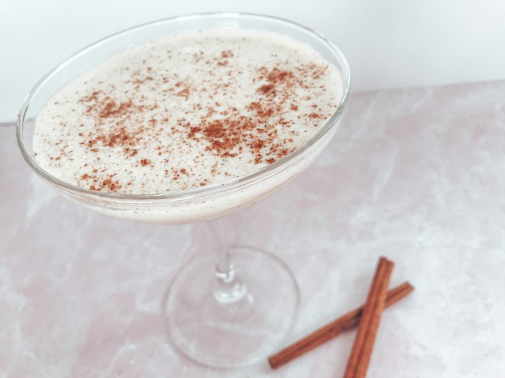 Nutmeg in a coup glass with nutmeg and cinnamon sticks