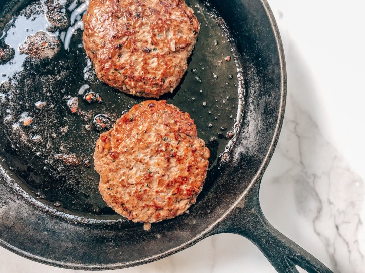 Two lamb burgers in a cast iron skillet