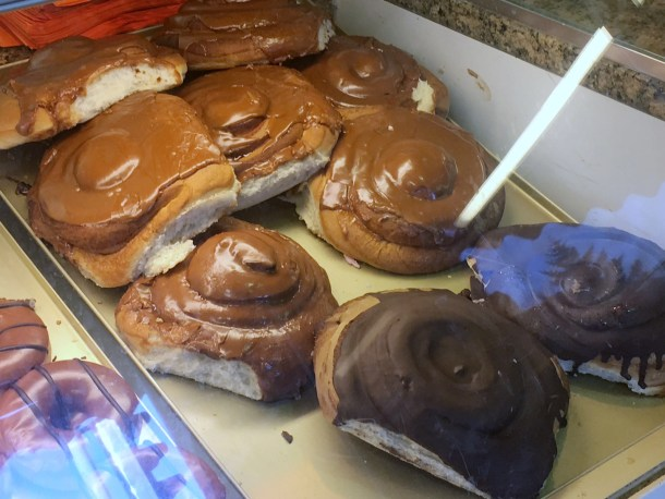 An image of a bakery case full of large, chocolate iced sweet rolls.