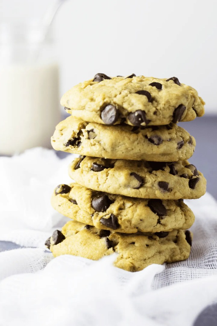 This is a stack of vegan chocolate chip cookies next to a large jar of ice cold oat milk. Perfect for an afternoon (or anytime) snack!