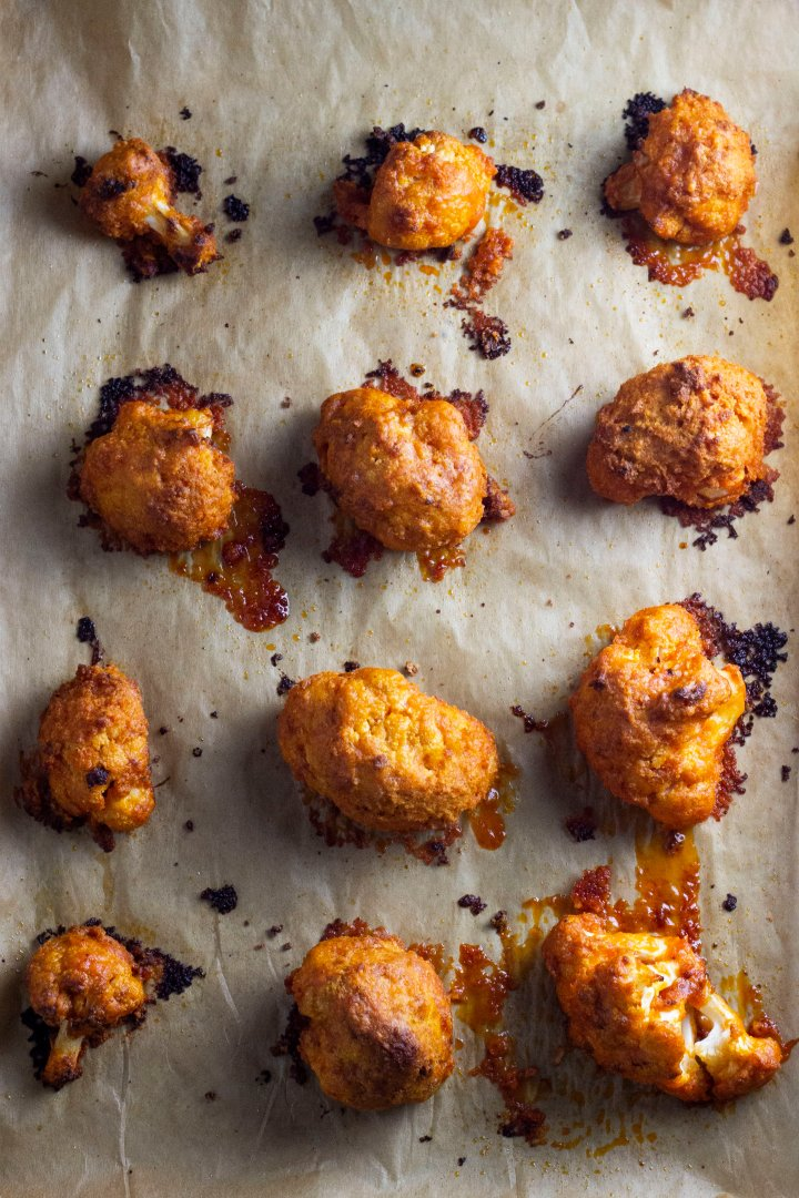 Buffalo cauliflower wings, already baked and breaded, on a baking tray covered in brown parchment paper. This is an overhead shot of one dozen buffalo cauliflower wings.