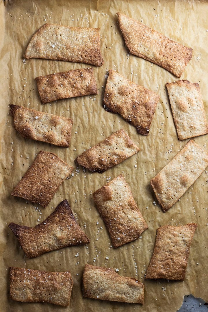 A baking tray full of crispy whole wheat crackers, fresh out of the oven on a piece of brown parchment paper.