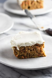 A slice of carrot cake on a small stoneware plate.