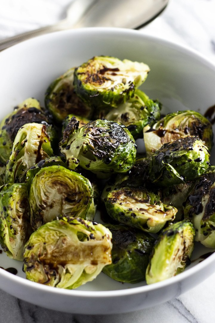 A closeup dish of roasted Brussels sprouts, topped with balsamic glaze.