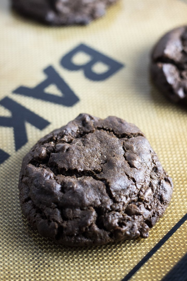 Closeup shot of one vegan double chocolate cookie on a silicone baking sheet.