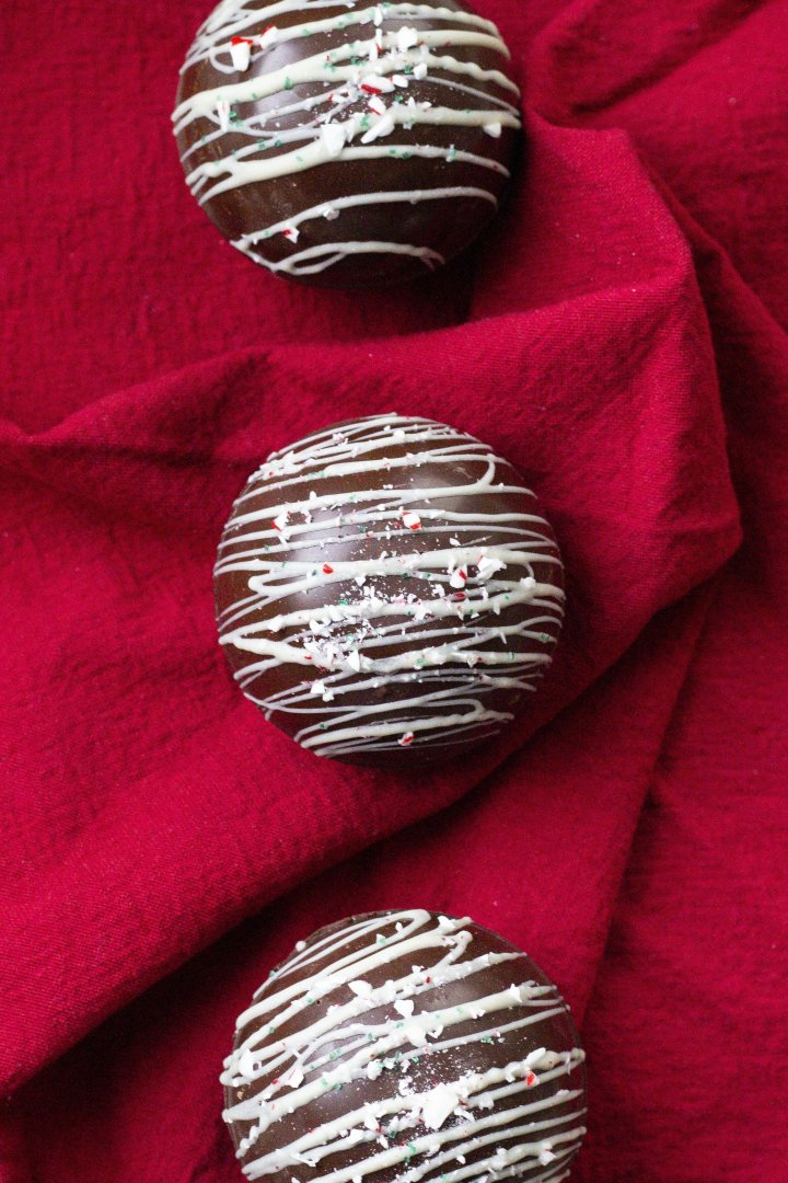 Overhead shot of three vegan hot chocolate bombs on a crinkled red napkin. The center bomb is drizzled with white chocolate and topped with crushed candy cane and green sprinkles.