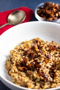 A 45-degree angle shot of caramelized onion risotto topped with coconut chip bacon.