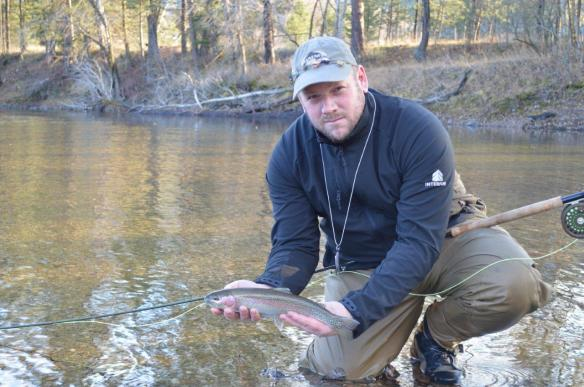 Brad Siemens (Grand Forks Wildlife Association) poses with a rainbow trout he is about to release on November 16. (Credit: Brad Siemens)