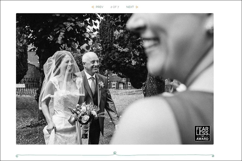 Fearless award winning image of a bride sticking her tongue out while walking to the church with her dad.