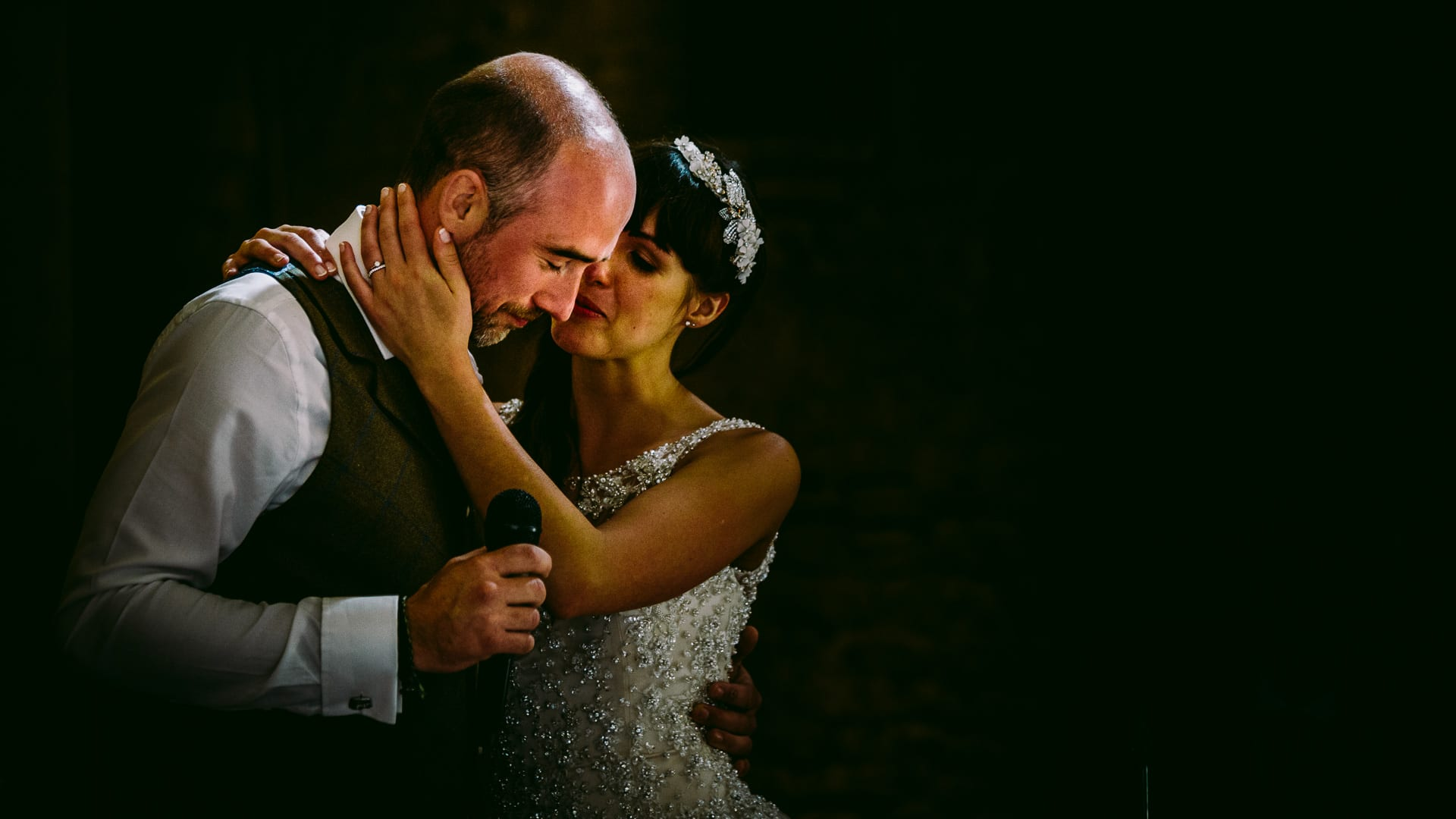 An emotional groom is held by his bride during his speech