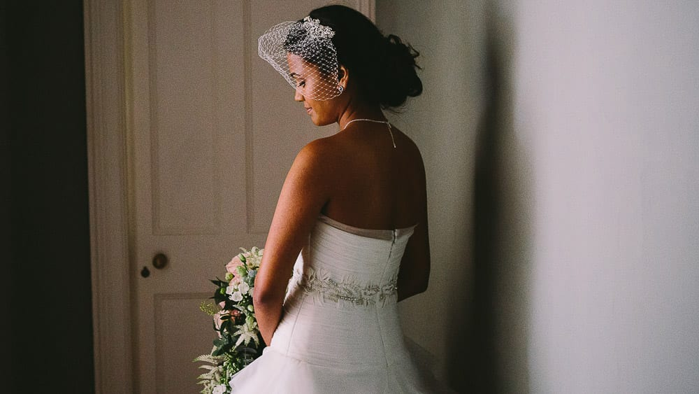 A portrait of the bride lit by a doorway before the ceremony