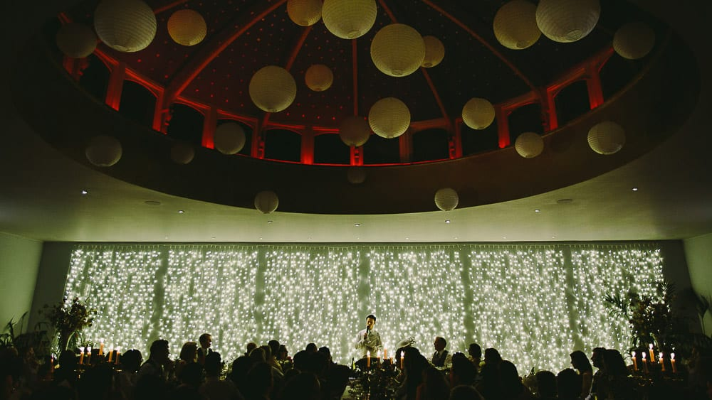 The groom gives his speech in front of a wall of lights a the matara centre