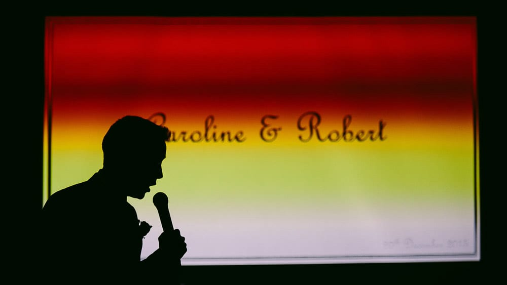 A silhouette of the best man giving his speech