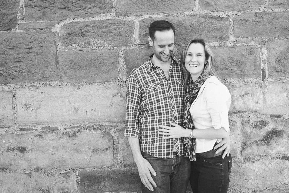 Black and white image of engaged couple leaning against a wall in Clifton