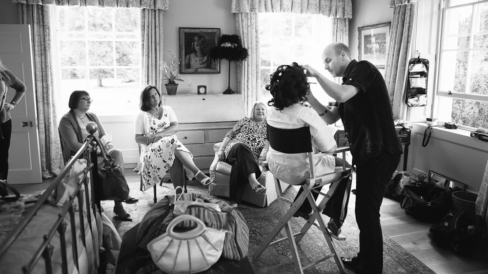 A bride having her makeup done while her bridesmaids look on at Rockley Manor