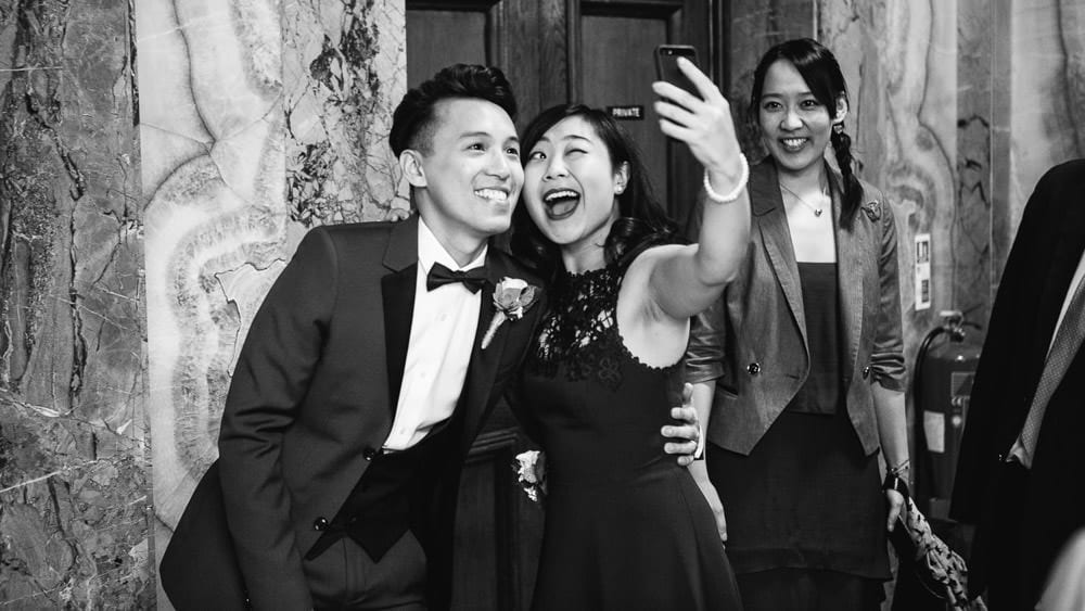 Black and white image of groom and bridesmaid taking a selfie
