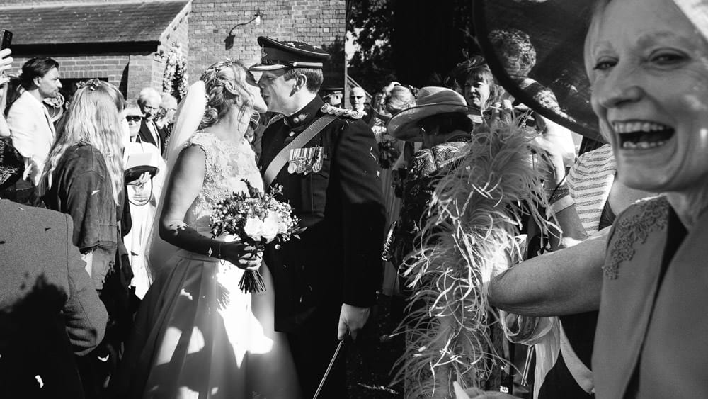 Military groom and his bride kissing under confetti