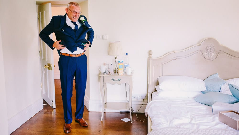 Brides father showing off his belt before Great Tythe Barn wedding