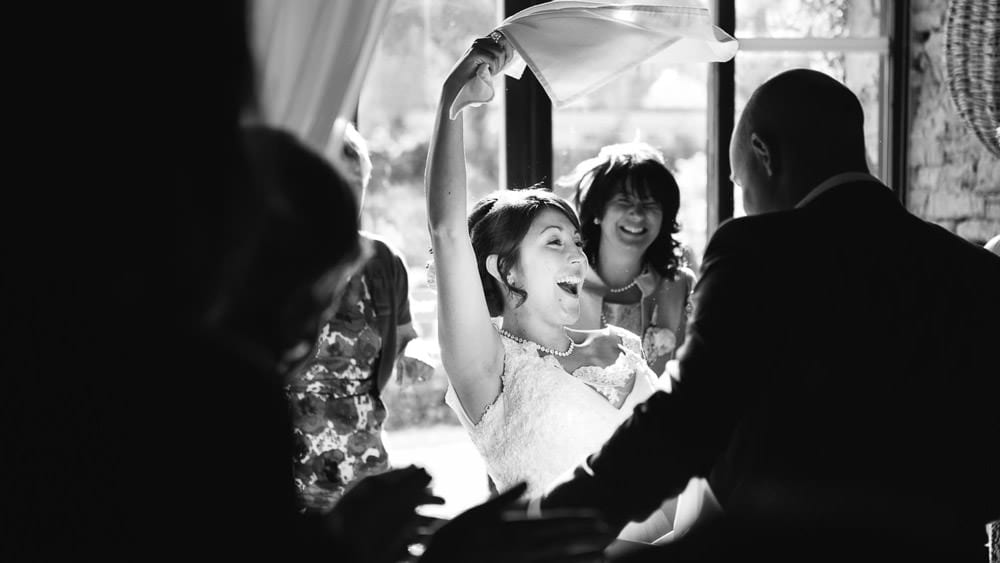 Black and white image of bride dancing to singing waiters at Great Tythe Barn