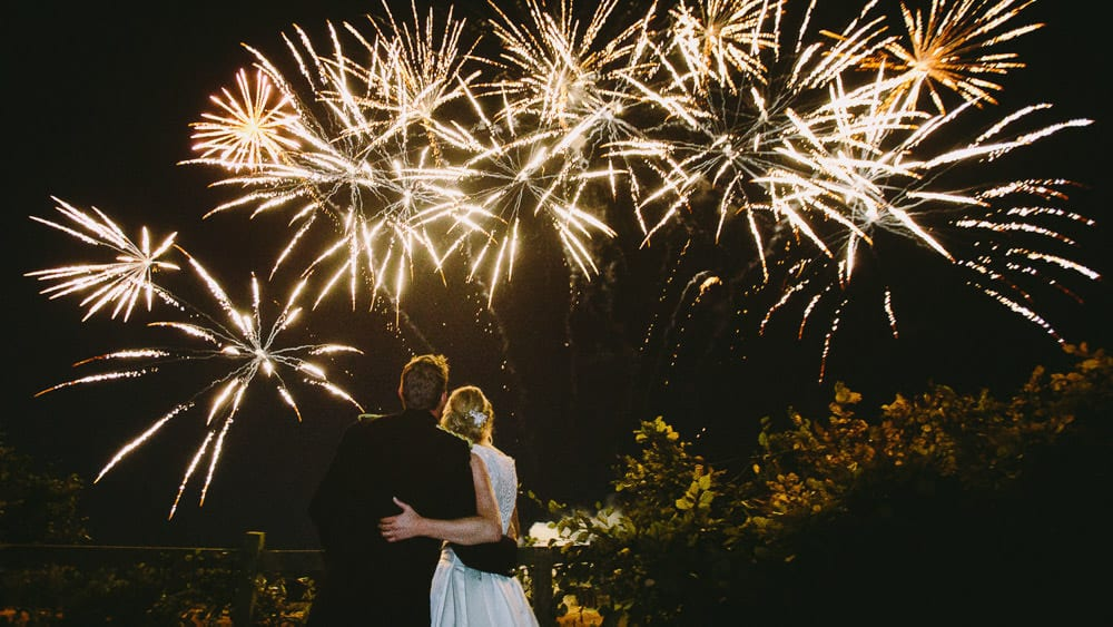 Bride and groom watching fireworks at military wedding