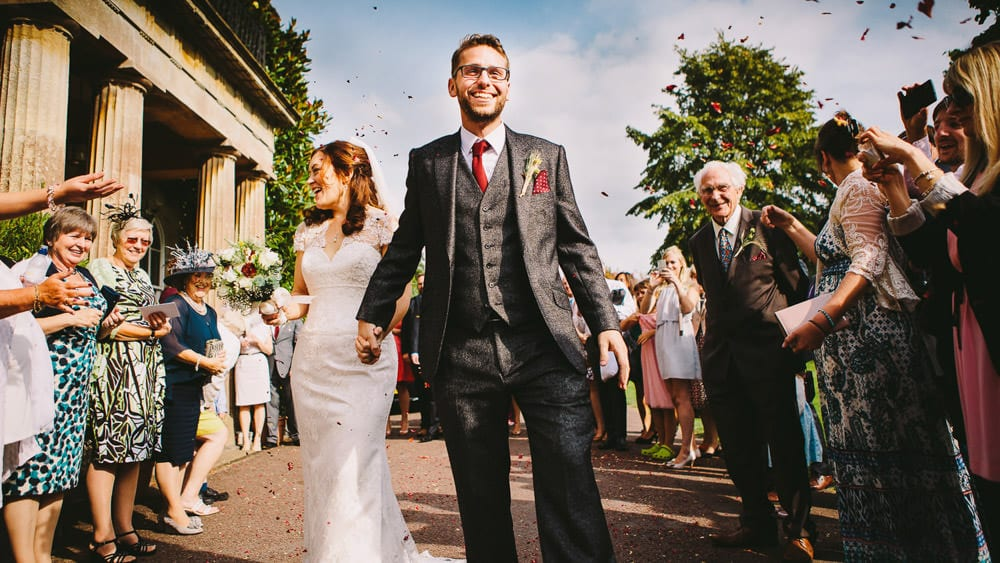 Bride and groom walk through confetti outside Harptree Court