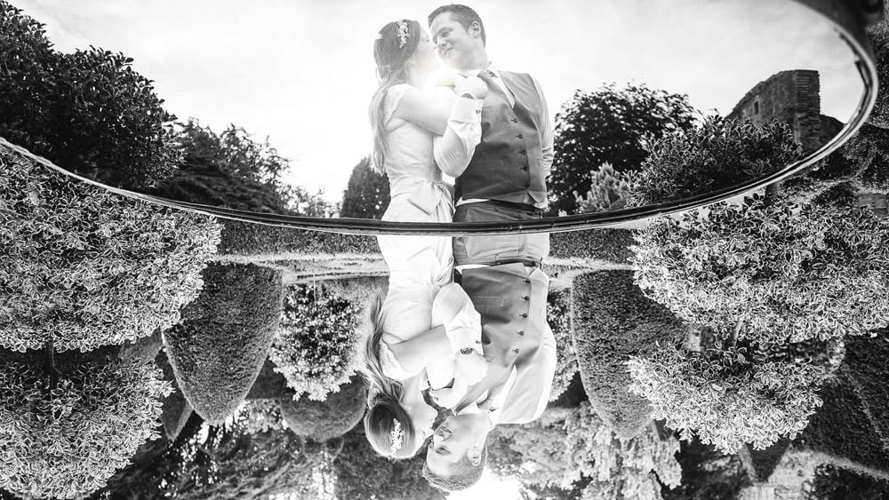 Bride and grooms reflection in a pool at Abbey House Gardens