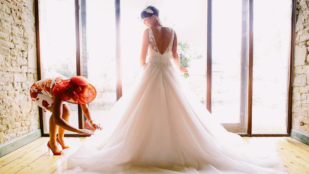 The brides mother arranges her dress