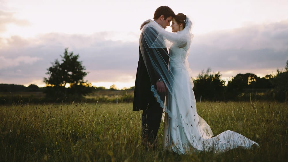The bride and groom with their heads together in the sunset