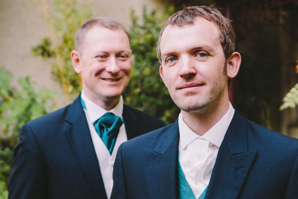 Groom and best man in the cloistered garden
