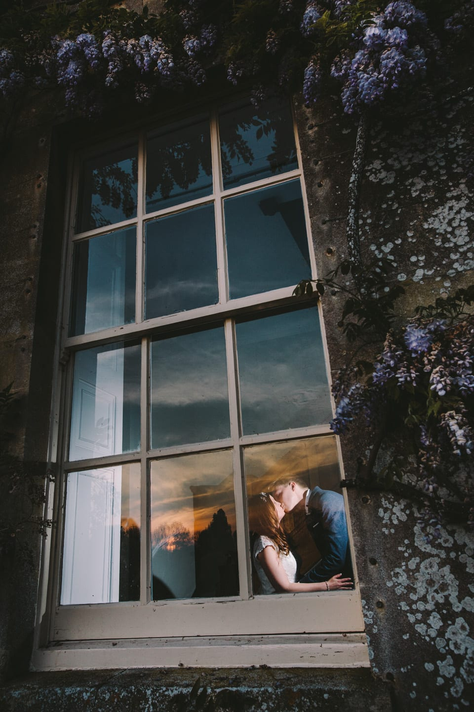 bride and groom kissing in a window at sunset