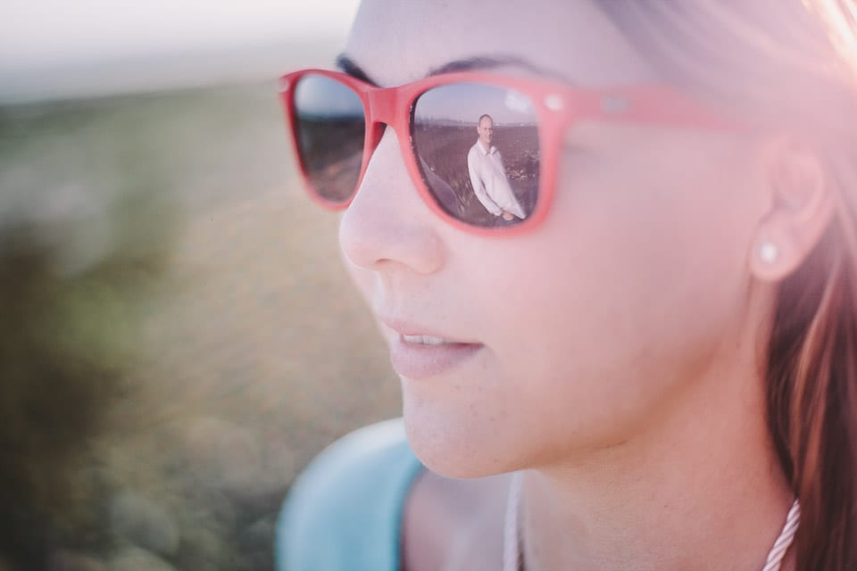 Engaged couple at Portchester Castle with groom to be reflected in sunglasses