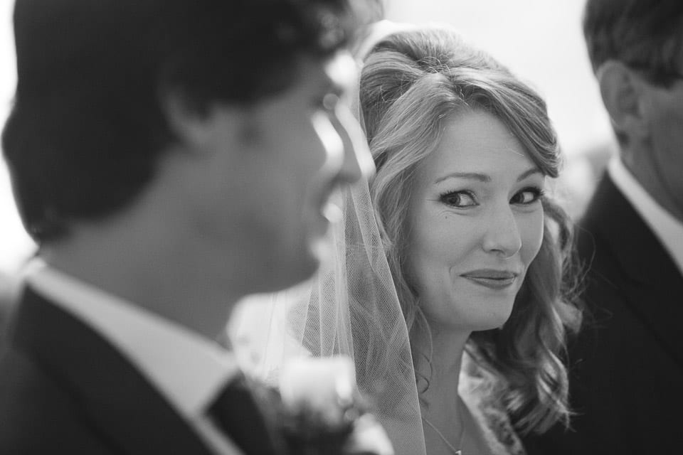 The bride smiling at the groom during the ceremony
