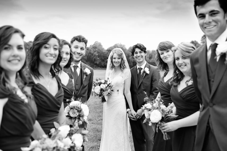 The bride, groom and wedding party lined up and smiling for a photo