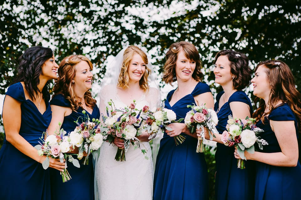 The bride and bridesmaids lined up and laughing at a joke