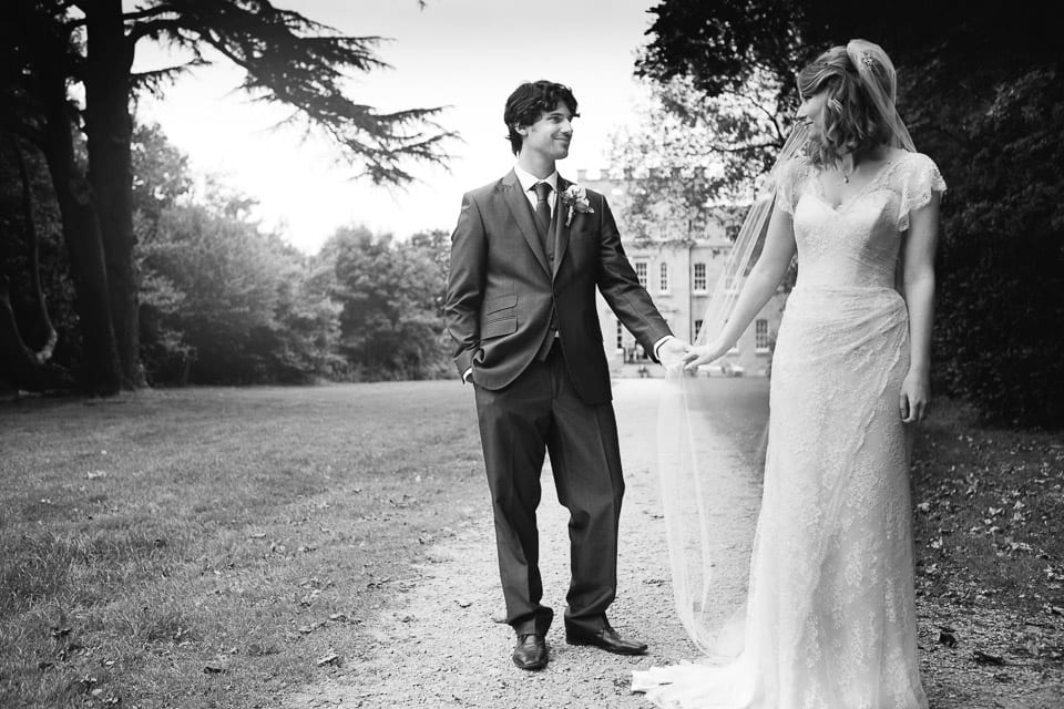 The bride and groom pose in the parkland