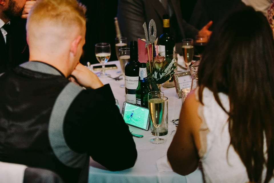 A guest watching football on his phone during the speeches